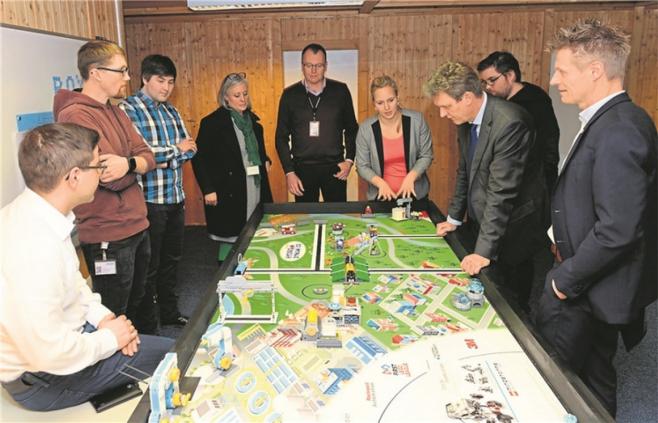 """Beeindruckt zeigte sich Lingens Oberbürgermeister Dieter Krone (Zweiter von rechts) von der Talentförderung beim Technologiekonzern Rosen. Ein Beispiel ist die Programmierung von Lego-Robotern, mit denen sich zurzeit eine Nachmittags-AG mit zehn Kindern in den Räumen von """"Royouth"""" beschäftigt. Foto: Thomas Pertz"""
